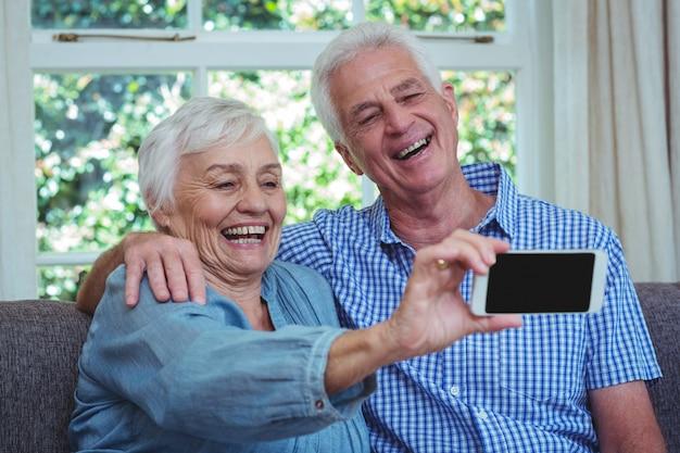 Lächelnde ältere paare, die selfie nehmen