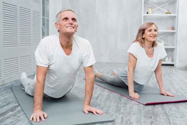 Lächelnde ältere paare, die übung zu hause ausdehnend durchführen