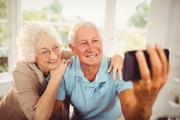 Lächelnde ältere paare, die zu hause selfie nehmen