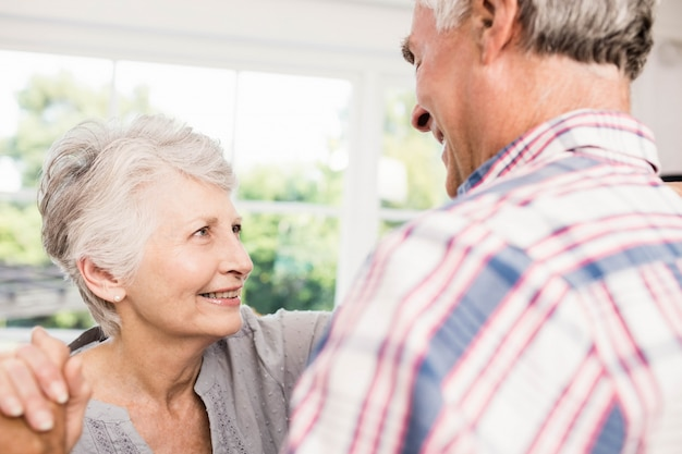 Lächelnde ältere paare, die zu hause tanzen