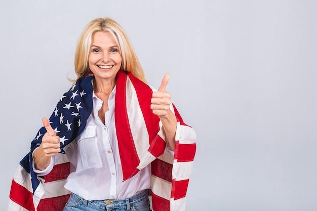 Lächelnde ältere schöne patriotische frau, die flagge der vereinigten staaten trägt lokalisiert über weißem hintergrund mit einem überraschungsgesicht.