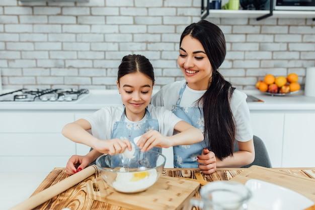 Lächelnde ältere schwester mit ihrem kleineren. mit eiern kochen