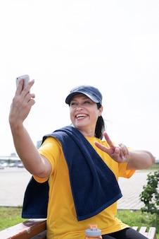 Lächelnde ältere sportlerin, die selfie draußen im park tut