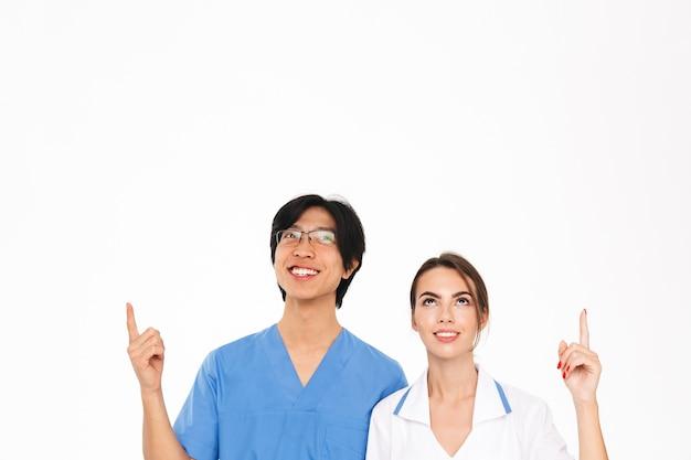 Lächelnde ärztepaar tragen uniform, die isoliert über weißer wand steht und auf kopierraum zeigt