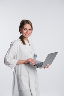 Lächelnde ärztin, die an ihrem laptop gegen ein weiß arbeitet
