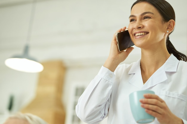 Lächelnde ärztin, die smartphone benutzt und heißes getränk trinkt