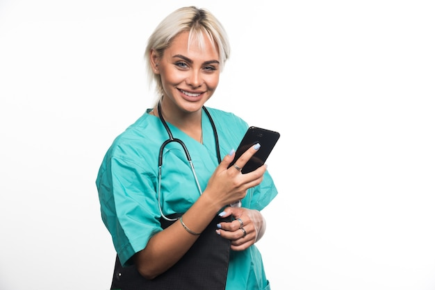 Lächelnde ärztin, die zwischenablage und telefon auf weißer oberfläche hält