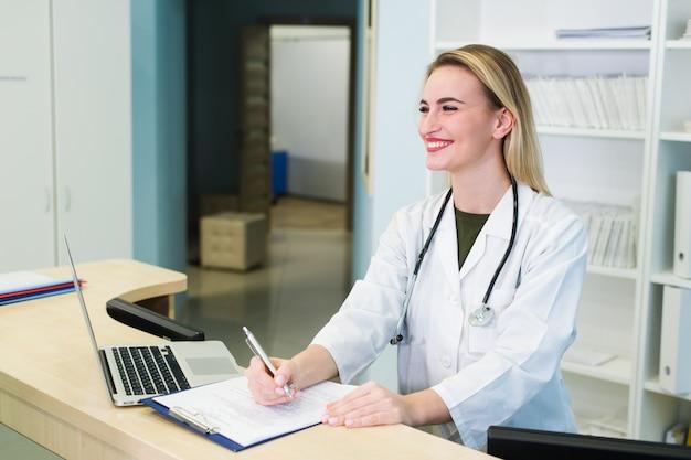 Lächelnde ärztin mit computer in ihrem büro im krankenhaus. junge attraktive kaukasische ärztin, die medizinische uniform trägt, die am schreibtisch sitzt