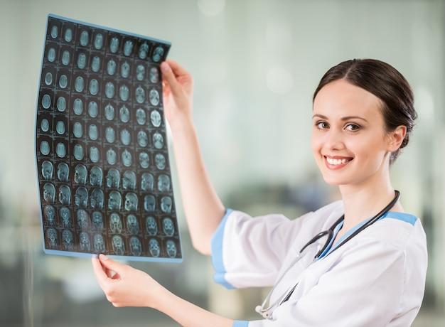 Lächelnde ärztin mit dem stethoskop, das röntgenstrahl betrachtet.