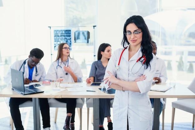 Lächelnde ärztin mit stethoskop, das vor dem sanitäterteam im krankenhaus steht. attraktive junge ärztin in weißem mantel und brille