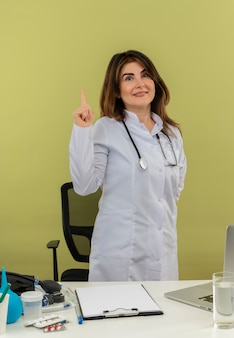 Lächelnde ärztin mittleren alters, die medizinische robe und stethoskop trägt, die hinter schreibtisch mit medizinischen werkzeugen und laptop stehen und finger heben, die hand hinter dem rücken isoliert halten