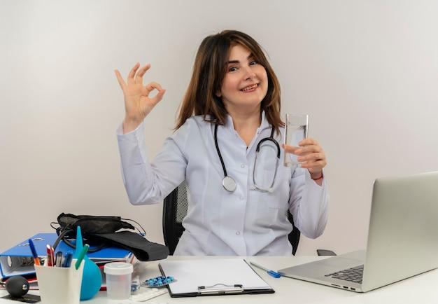Lächelnde ärztin mittleren alters, die medizinische robe und stethoskop trägt, sitzt am schreibtisch mit medizinischen werkzeug-zwischenablage und laptop, die ok zeichen halten glas des wassers isoliert halten