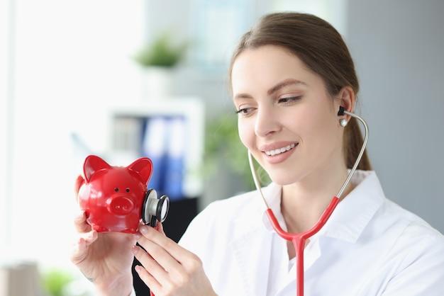 Lächelnde ärztin stethoskop hört sparschwein sparschwein