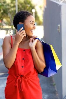 Lächelnde afrikanische frau, die am handy mit einkaufstaschen spricht