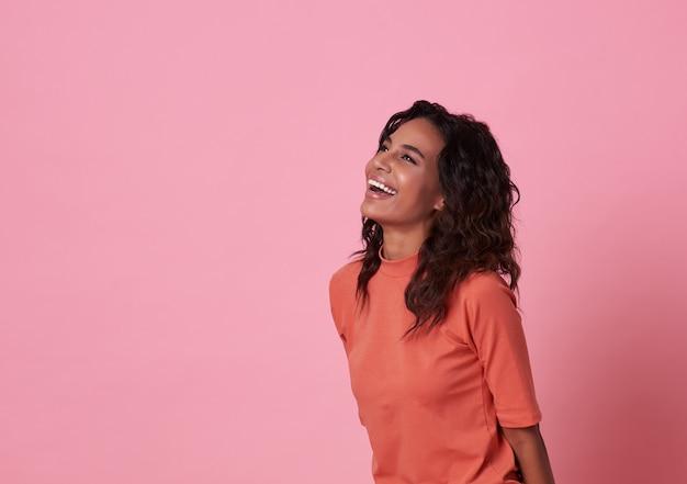 Lächelnde afrikanische frau, die den kopienraum trägt das zufällige orange t-shirt lokalisiert auf rosa betrachtet.