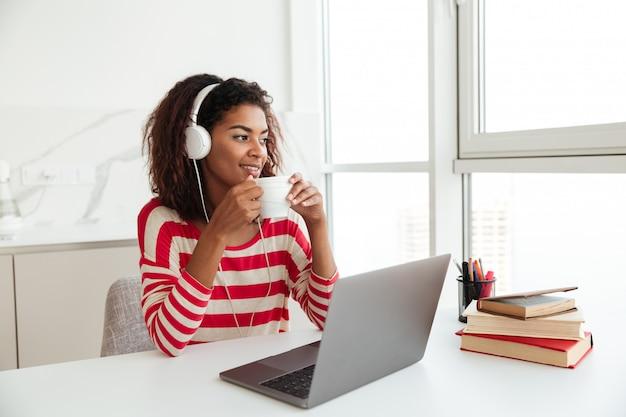 Lächelnde afrikanische frau, die durch den tisch mit laptop-computer sitzt