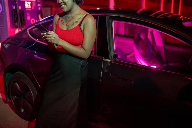 Lächelnde afrikanische frau, die im smartphone eine sms schreibt, während ihr auto aufgeladen wird