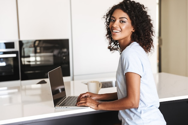 Lächelnde afrikanische frau mit laptop-computer
