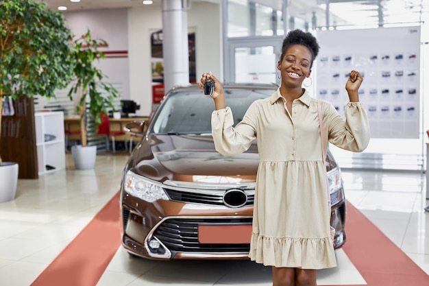 Lächelnde afrikanische frau mit schlüsseln von ihrem neuen auto