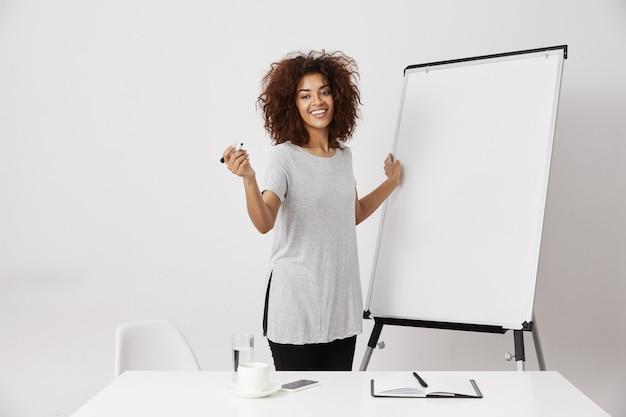 Lächelnde afrikanische geschäftsdame, die nahe leerem trockenem whiteboard im offenen raum des büros steht und ihre anwendungsidee oder einen geschäftsplan über weißer wand erklärt.