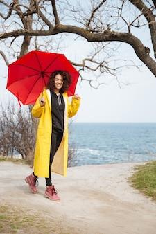 Lächelnde afrikanische lockige junge dame, die gelben mantel hält regenschirm trägt