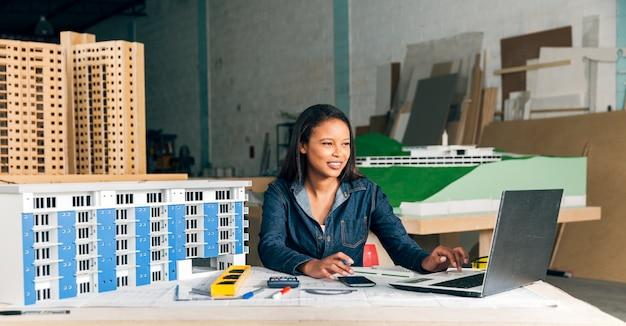Lächelnde afro-amerikanische dame mit laptop und modell des gebäudes