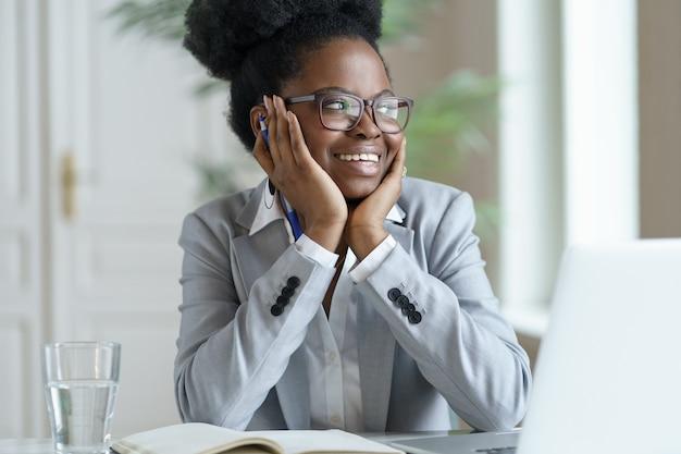 Lächelnde afro-frau im blazer tragen brille, die am laptop-computer zu hause arbeitet und wegschaut.
