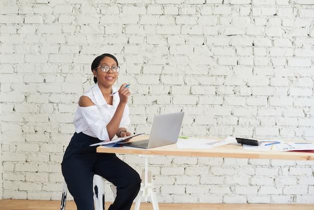 Lächelnde afro-geschäftsfrau, die an laptop arbeitet und notizen im modernen büro macht. platz kopieren.