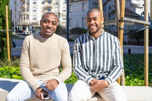 Lächelnde afroamerikaner sitzen auf bank mit telefonen