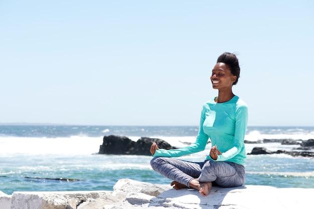 Lächelnde afroamerikanerfrau, die yoga durch das meer tut