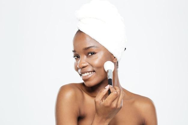 Lächelnde afroamerikanerin beim schminken mit pinsel auf weißem hintergrund isolated