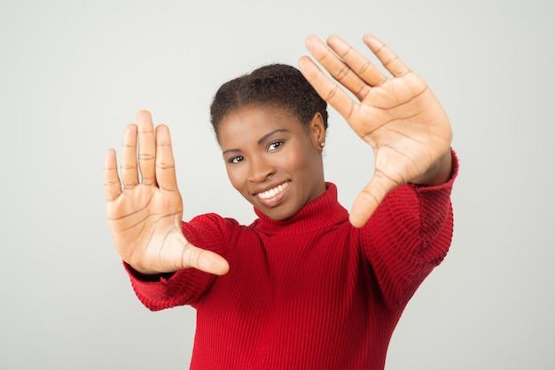 Lächelnde afroamerikanerin, die fotorahmen mit händen macht