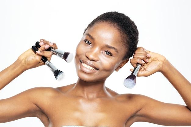Lächelnde afroamerikanerin, die make-up-pinsel auf weißem hintergrund hält
