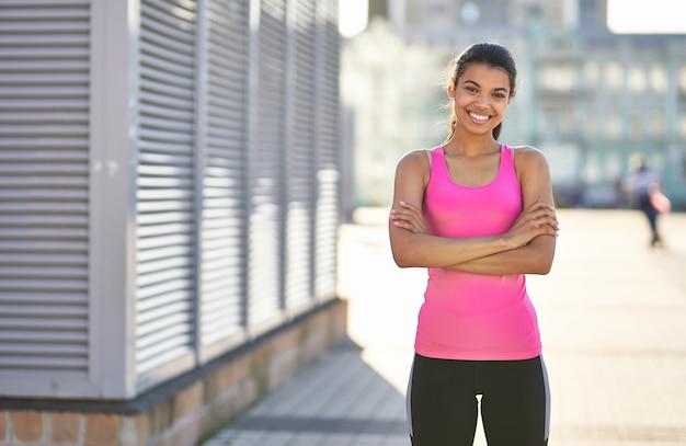 Lächelnde afroamerikanische dame im hellen sport-t-shirt im freien