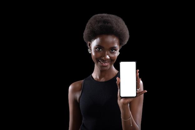 Lächelnde afroamerikanische schwarze frau, die auf leeren weißen bildschirm des mobiltelefons mit kopienraum zeigt, isoliert