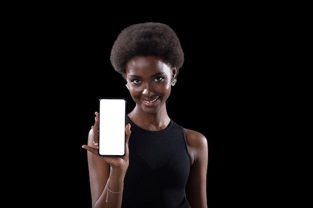Lächelnde afroamerikanische schwarze frau, die mit dem finger auf den weißen bildschirm des leeren vorlagenhandys auf schwarzem hintergrund zeigt