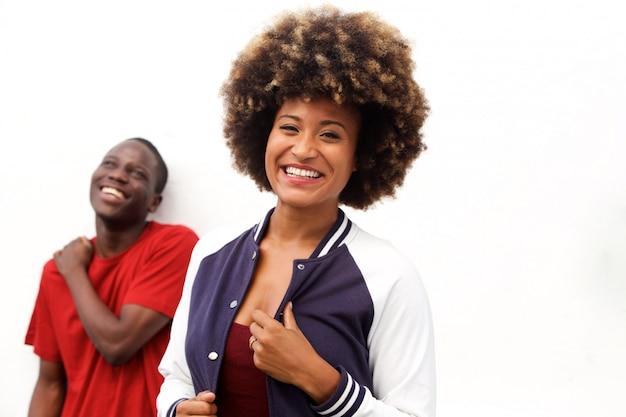 Lächelnde afrocan amerikanische frau mit dem mann, der im hintergrund steht