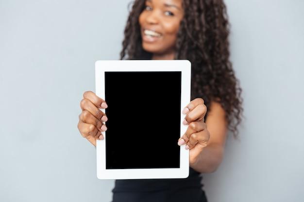 Lächelnde afrofrau, die leeren tablet-computer über grauer wand zeigt