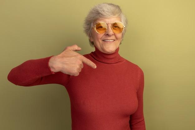 Lächelnde alte frau mit rotem rollkragenpullover und sonnenbrille, die auf den raum vor ihr zeigt, isoliert auf olivgrüner wand mit kopierraum