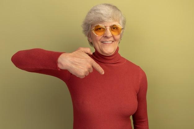 Lächelnde alte frau mit rotem rollkragenpullover und sonnenbrille, die nach vorne nach unten zeigt, isoliert auf olivgrüner wand mit kopierraum