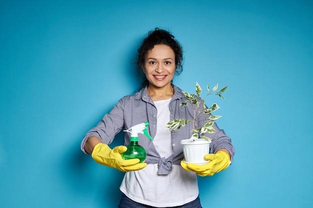 Lächelnde amerikanerin in gelben handschuhen, die einen topf mit transplantiertem kleinen baum und spray für zimmerpflanzen halten.