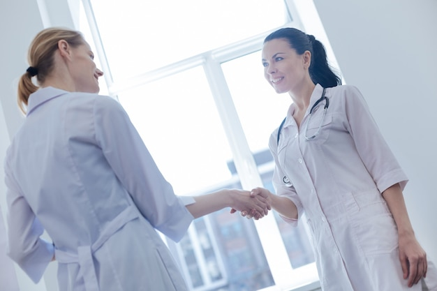 Lächelnde angenehme junge krankenschwestern, die in der klinik stehen und unterhaltung beim händeschütteln genießen