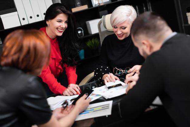 Lächelnde angestellte, die an arbeitsplatz sprechen