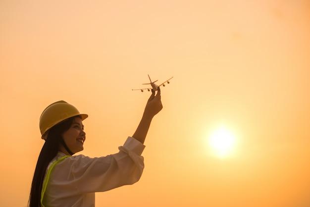 Lächelnde angestelltfrau, die flugzeug in den händen mit sonnenuntergang hält