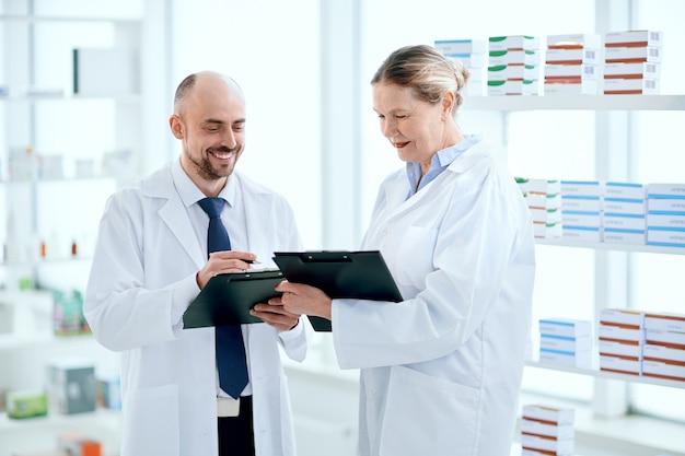 Lächelnde apotheker besprechen etwas, das in der nähe des regals mit medikamenten steht