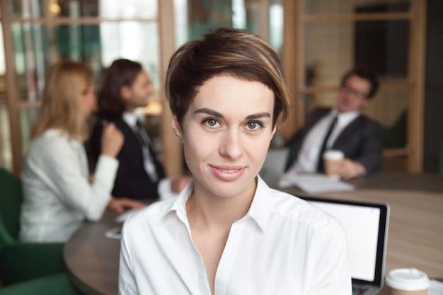 Lächelnde arbeitnehmerin, die für firmengeschäftskatalog aufwirft