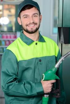 Lächelnde arbeitskraft an der tankstelle, beim füllen eines autos.