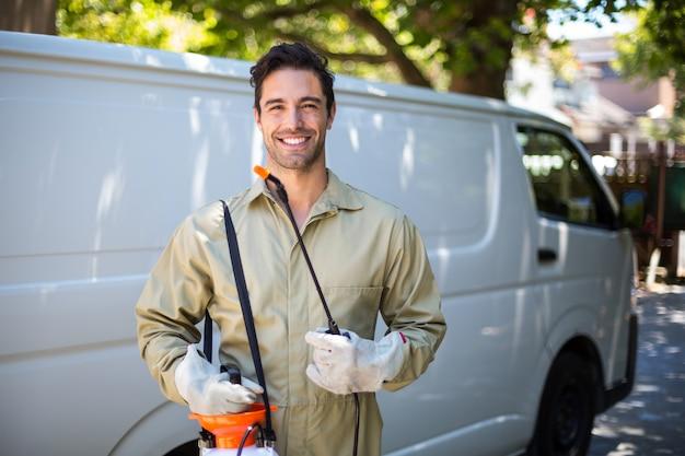 Lächelnde arbeitskraft mit pestizidsprüher