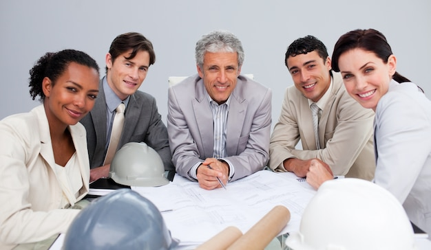 Lächelnde architekten in einer sitzung pläne studierend