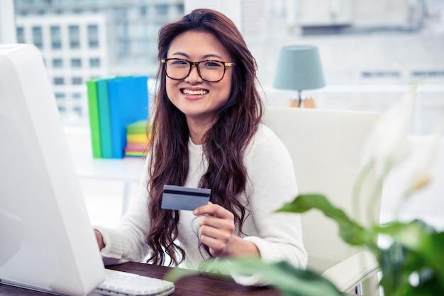 Lächelnde asiatin auf dem computer, der kreditkarte im büro hält